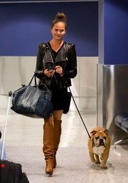 Chrissy Teigen was moto-chic in a black leather jacket and tan knee-high boots as she arrived at LAX.