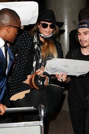 Chrissy Teigen tried to go incognito (but failed) with a pair of Balenciaga cateye sunnies and a hat as she arrived at LAX.