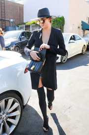 Chrissy Teigen teamed open-toe, thigh-high boots with a long black blazer for a lunch out in LA.