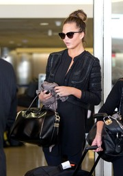 Chrissy Teigen layered a textured black cropped jacket over a tunic for her super-stylish travel look.