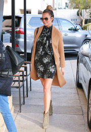 Chrissy Teigen layered on a camel-colored coat for some warmth.