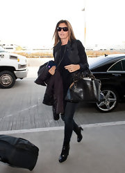 Cindy Crawford accented her chic airport style with a slightly Victorian-style bowler.
