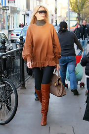 Claudia Schiffer strolls the street in this lovely camel sweater and over the knee boots.