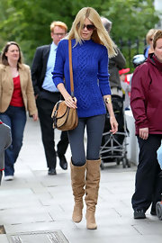 Claudia Schiffer bundled up in London in slouchy sand suede over-the-knee boots.
