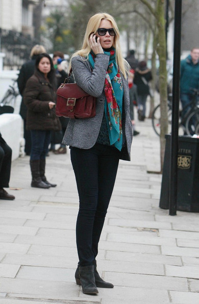 Claudia brightens up her casual day look with a red leather shoulder bag with brushed metal hardware.