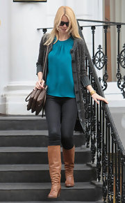 Claudia wears a loosely fitted bright blouse with her neutral toned ensemble.
