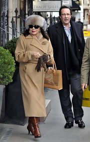 Joan Collins showed off her signature classic glamorous style with this camel-colored wool coat.