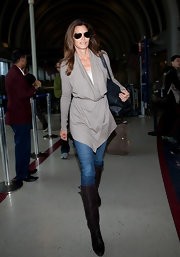 Ageless beauty Cindy Crawford accessorized her look with brown leather knee-high boots.