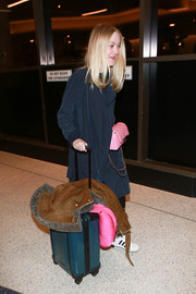 Dakota Fanning made her way through LAX pushing a blue rollerboard.