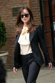 Dakota Johnson paired a pale-yellow ruffle blouse with a black suit, both by Gucci, for a day out in New York City.