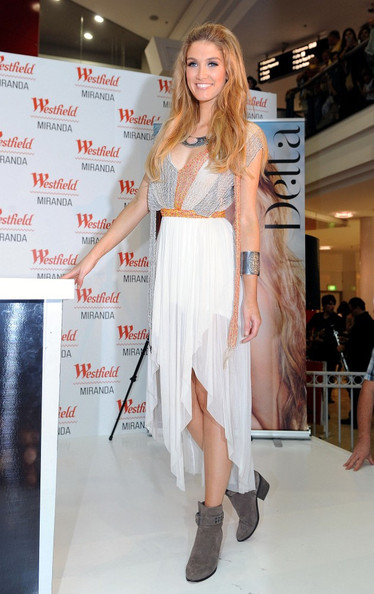 Delta Goodrem paired a feminine dress with gray suede ankle boots for a performance at a Sydney mall.