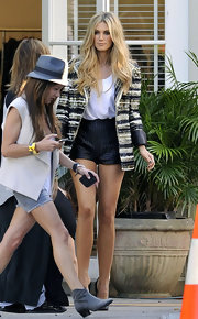 Delta Goodrem showed off her tan legs in a pair of black leather like high-waist shorts.