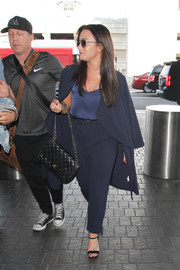Demi Lovato was spotted at LAX looking business-chic in a navy duster and pants combo by Never Fully Dressed.