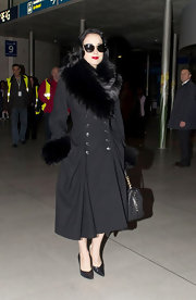 Dita traveled in a luxe fur-trimmed coat and black stilettos.
