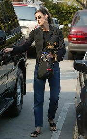 Demi wears a pair of classic blue jeans while carrying her dog.