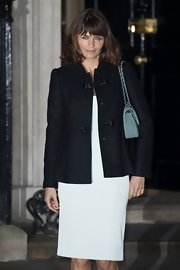 Helena Christensen paired a classic black wool coat with her white dress while attending a London reception.