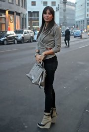 Elisabetta dons a warp sweater with a leather buckle for her stylish street wear.