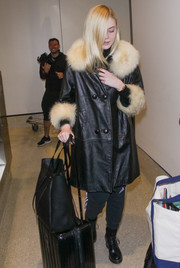 For her travel bags, Elle Fanning chose an oversized black tote and a Tumi suitcase.