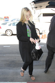 Elle Fanning topped off her airport ensemble with a simple black leather tote.