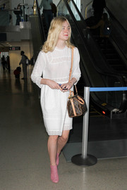 Elle Fanning looked adorable in her white baby doll dress while making her way through LAX.