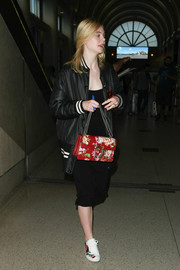 Elle Fanning touched down at LAX wearing an oversized black bomber jacket over an LBD.