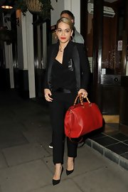 Rita added some color to her all-black look by carrying this crimson tote with bamboo-like handles.