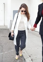 Emilia Clarke paired a white trench coat with a white blouse for a light and airy daytime look.