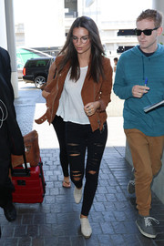 Emily Ratajkowski caught a flight at LAX looking edgy in a brown Veda suede jacket layered over a white shirt.