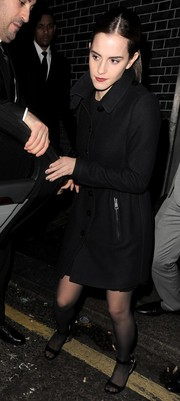 Emma Watson kept warm with an elegant black wool coat as she left a Lady Gaga show.