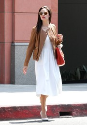 Emmy Rossum layered a boxy tan leather jacket over a little white dress for a day out in Beverly Hills.