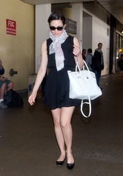 Emmy Rossum completed her travel get-up with a stylish white cross-body tote.