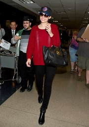 Emmy Rossum chose a scoopneck sweater in a bold red hue for her travel look.