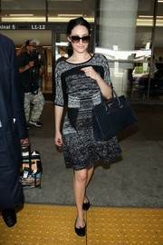 Emmy Rossum kept it comfy yet chic in a monochrome knit dress during her flight to LAX.