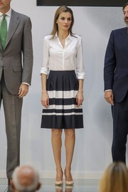 Princess Letizia styled her blouse with a flared blue and white skirt.