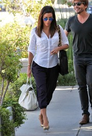Eva Longoria teamed her shirt with navy capri pants by Ramy Brook.