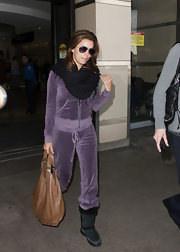 Eva wears a thick black pashmina with her lilac track suit.