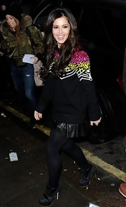 Cheryl got funky in this patterned sweater and black leather mini while out in London.