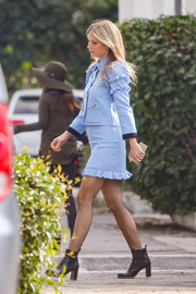 Gwyneth Paltrow sported a military-meets-girly vibe with this pastel-blue ruffle skirt suit by Gucci while out and about.