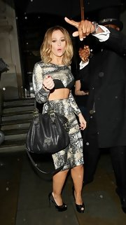 Kimberley Walsh wowed with this black cross-body tote and midriff-baring dress combo while out and about in London.