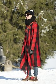 Anne Hathaway stayed bundled in Switzerland wearing this red and black checkered blanket coat. Cozy!