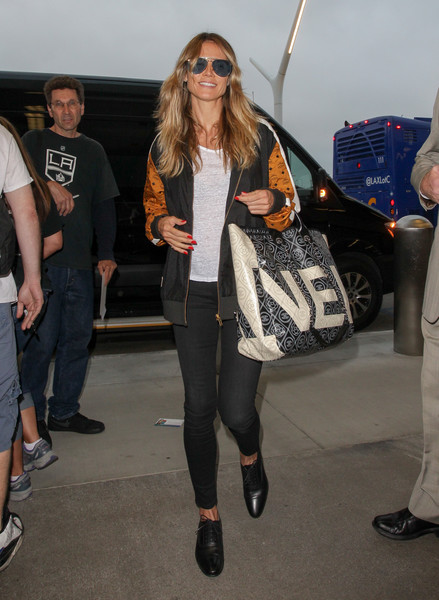 Heidi Klum finished off her travel attire with an oversized Chanel logo bag.