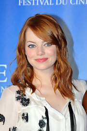 At 'The Help' photocall in Venice, Emma Stone wore her hair in carefree waves. To produce a similar effect, allow wavy hair to dry naturally, then spritz with a product like Living Proof Wave Shaping Spray. To finish, use fingers to separate individual waves.