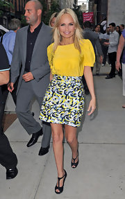 Kristin Chenoweth paired a sunny top with black Givenchy heels and a printed skirt.
