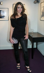 Elizabeth Hurley added glitz to her sexy black ensemble with a silver satin clutch.