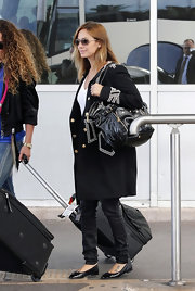 Natalie Imbruglia paired black ballet flats with a military coat for her traveling attire.