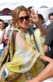 Jennifer looked glamorous in a flowing yellow frock paired with gold-embellished aviator sunglasses.