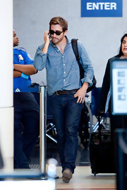 Jake travels in style through LAX wearing a denim button down shirt.