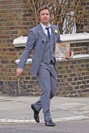 Jamie Oliver looks all business in his gray three piece suit.