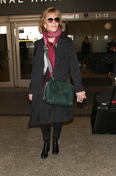 Jane Fonda arrived on a flight at LAX wearing a classic black trenchcoat.