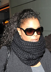 Janet is rocking black oversized sunglasses. They have a unique temple detail that shows her style.